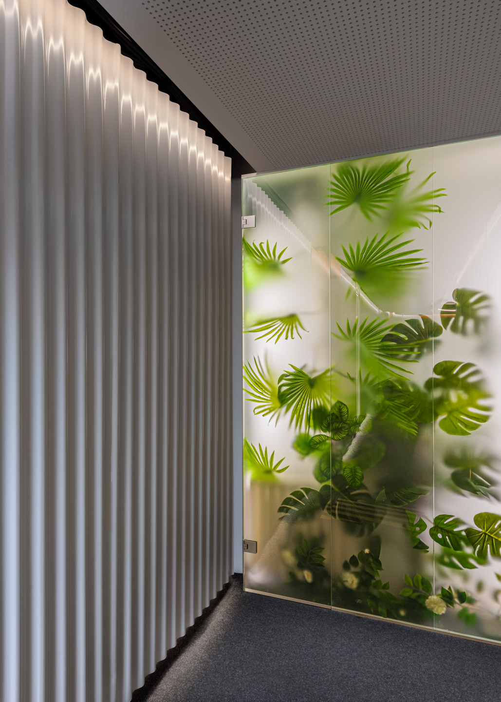 Surreal interior design with waving wall panels, concealed lighting and a tropical garden behind glowing frosted glass panes