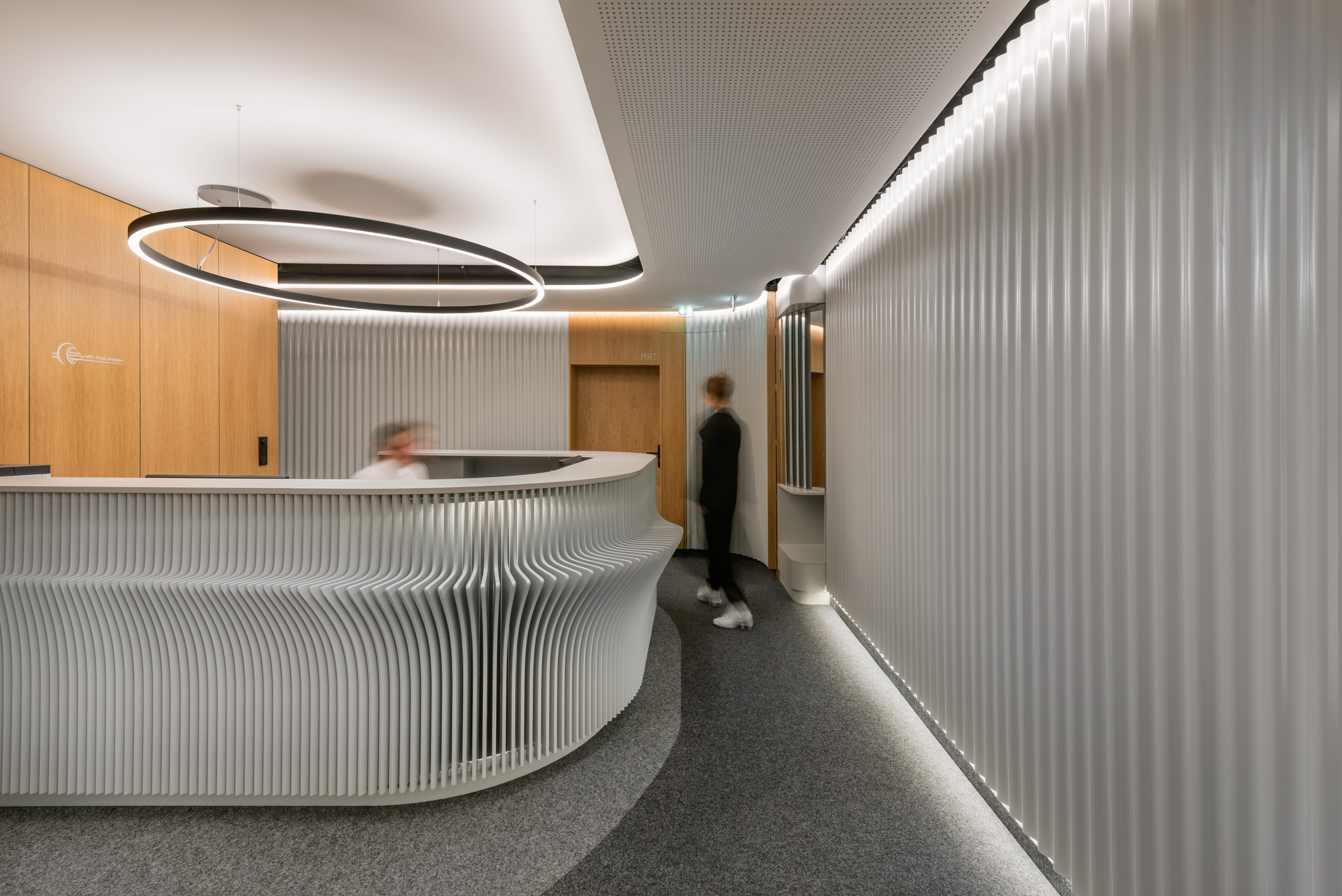 Reception room of a radiology center displaying wood paneled walls, accentuated lighting and a futuristic reception desk