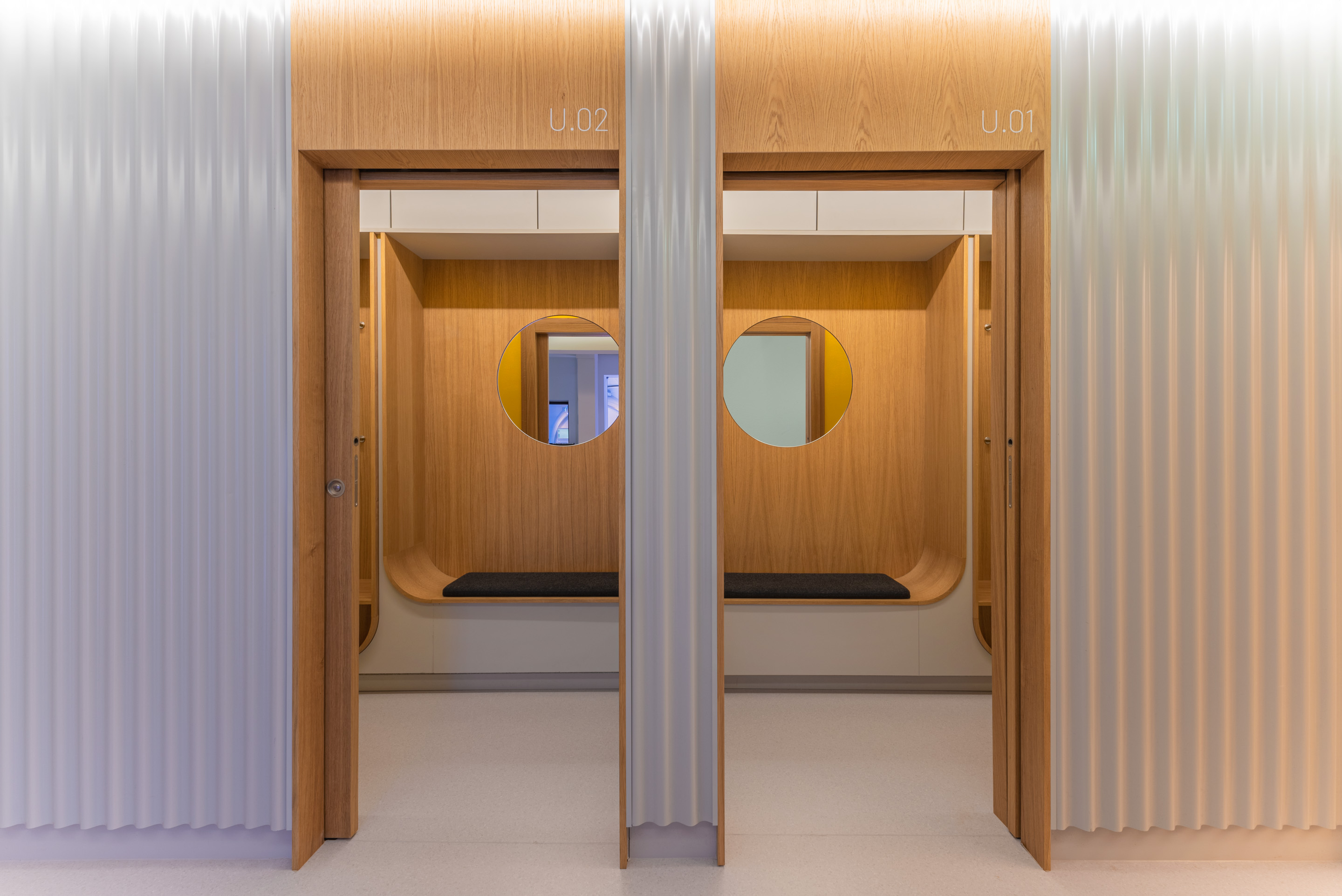 Dressing rooms with custom built wood furniture and doors, round mirrors and light grey waving metal wall paneling