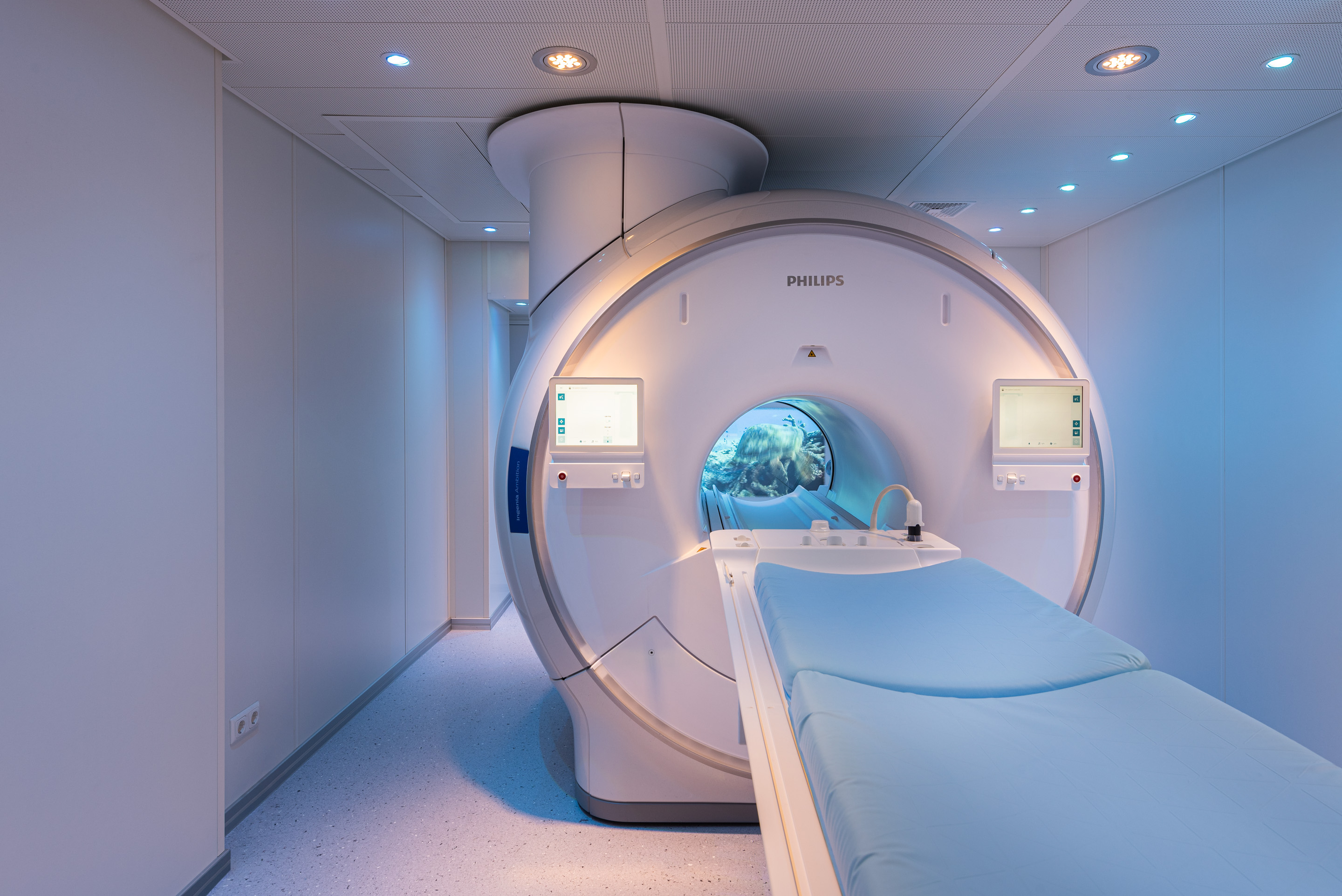Magnetic resonance imaging room with atmospheric color lighting and video projections integrated into the MRI tube