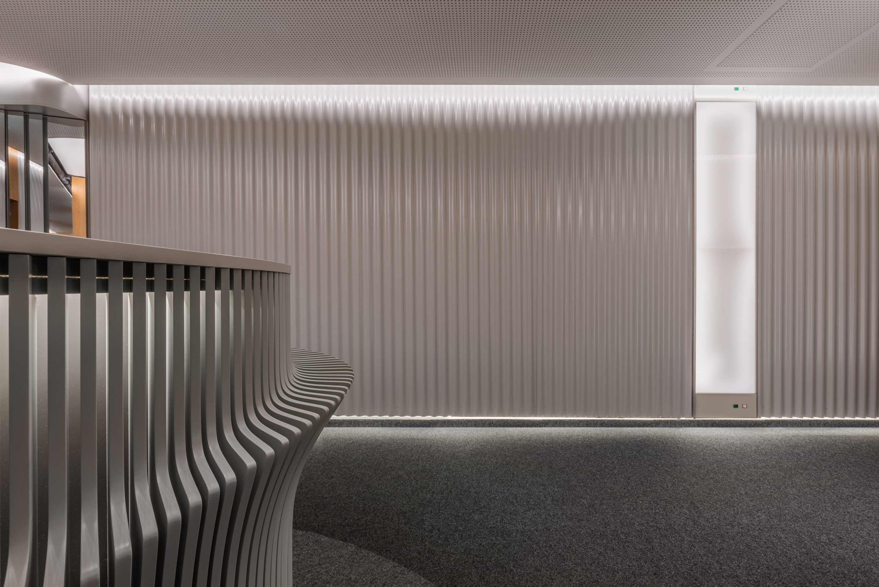 Soft waved light grey wall panelling with concealed floor and ceiling lighting and wall mounted x-ray lightbox