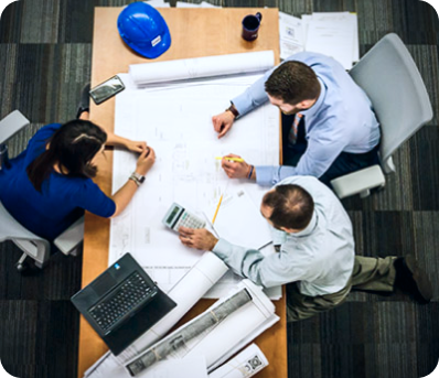 Team of workers gathered around blueprint on table