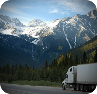 Semi truck driving on road with mountains in the background