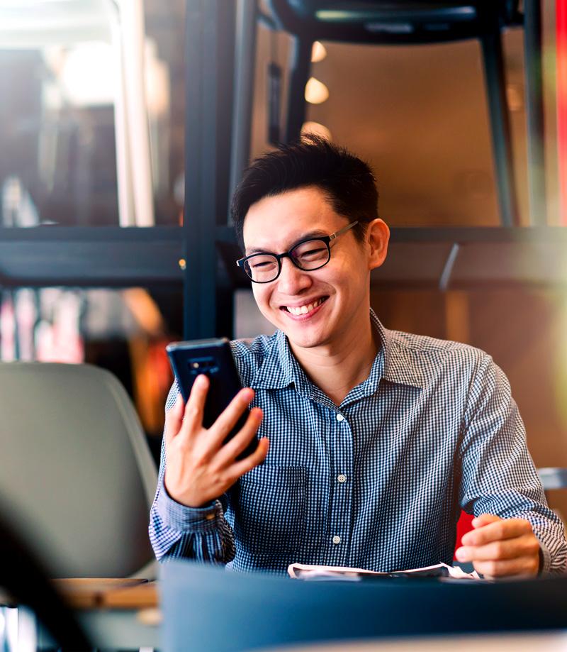 Man looking at his phone laughing