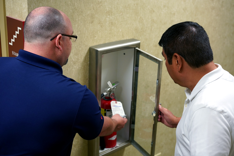 Men discussing safety protocols with fire extinguisher