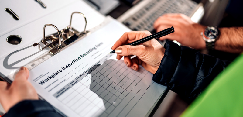 Hands holding a workplace inspection form on clipboard
