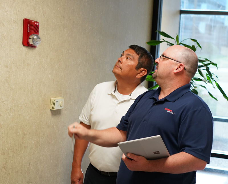 Two men discussing safety protocols with fire alarm