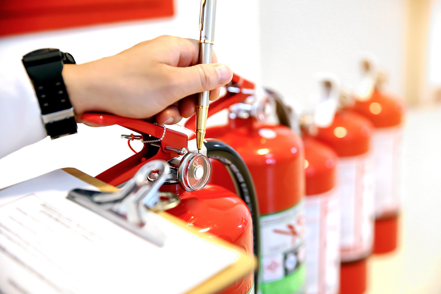 A person with fire extinguishers reviewing for safety