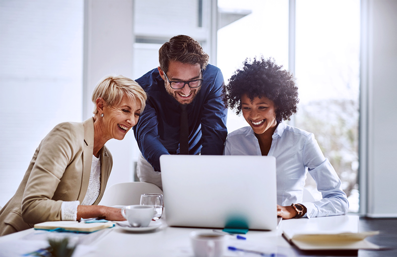 Three coworkers gathered around a computer laughing and working