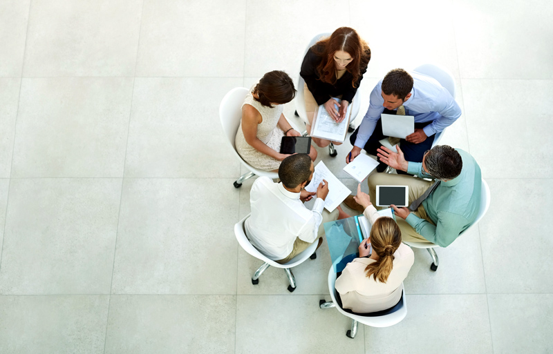 A team of workers gathered in a circle discussing information from papers and computers