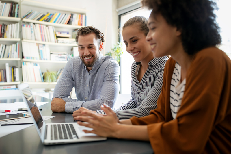Three coworkers gathered around computer smiling