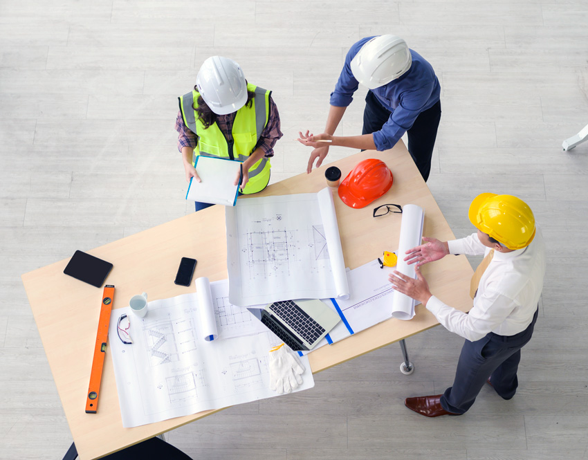 A team of construction workers gathered around a table with blueprints on it.
