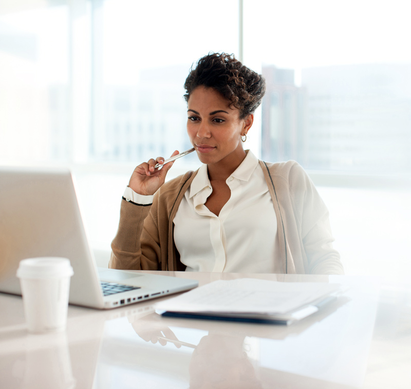A woman in deep thought looking at laptop at her desk
