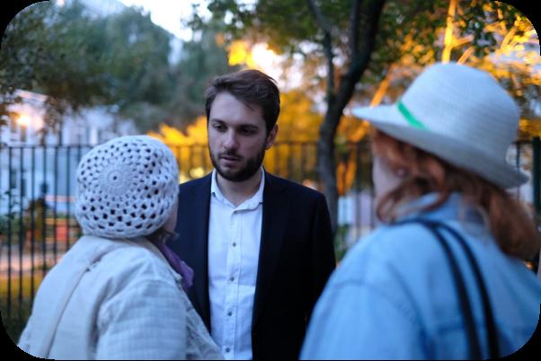 Фотография Романа Юнемана, обдающегося с двумя жителями, чьих лиц не видно