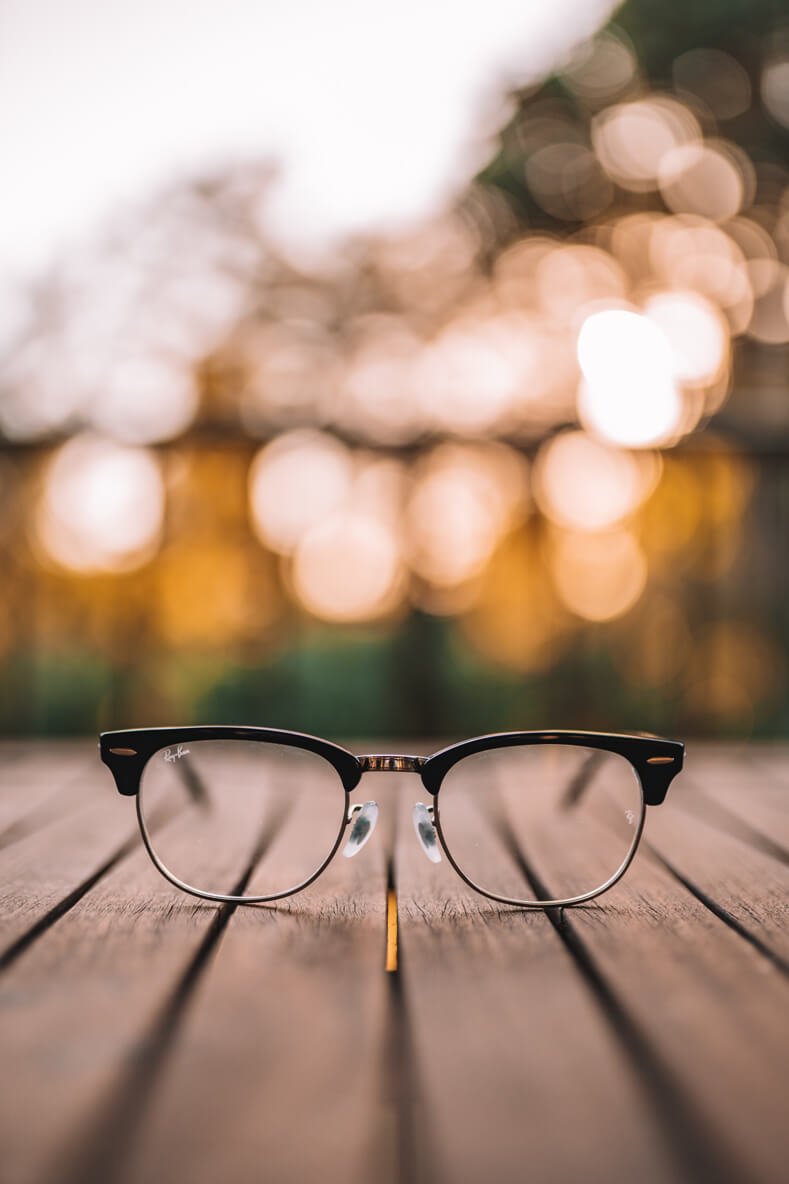 A pair of glasses sat outdoors with a soft-focus green and gold background.