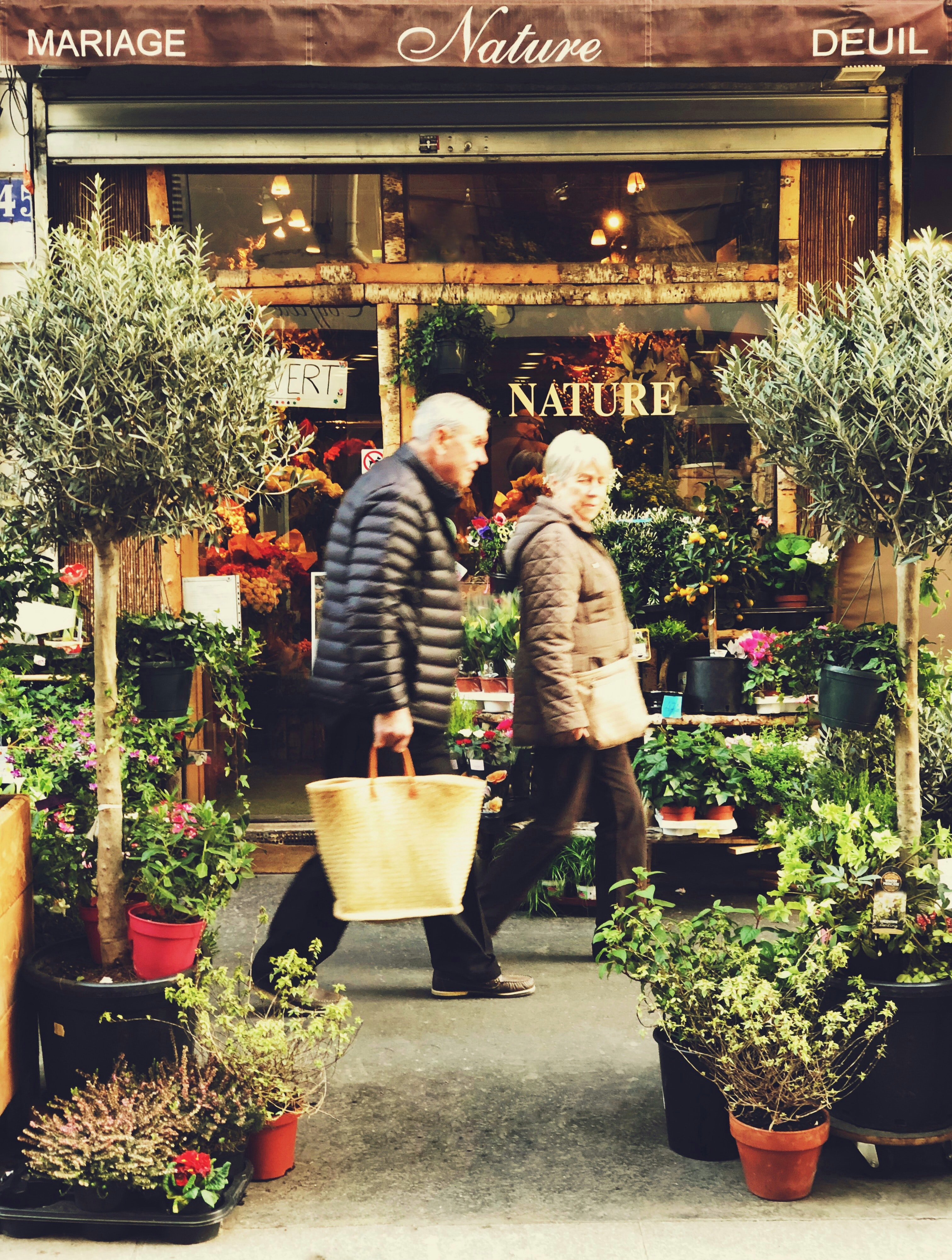 older couple walking by plant store