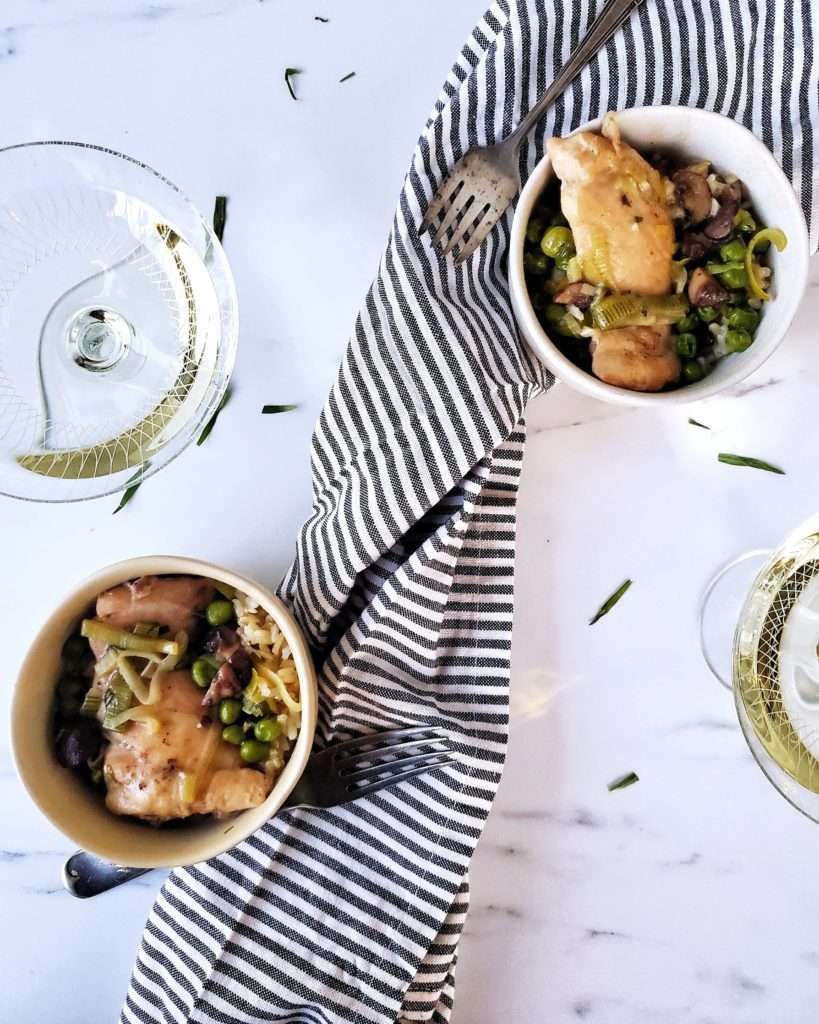 Small Bowls of Braised Chicken Thighs and Leeks with Glasses of Wine