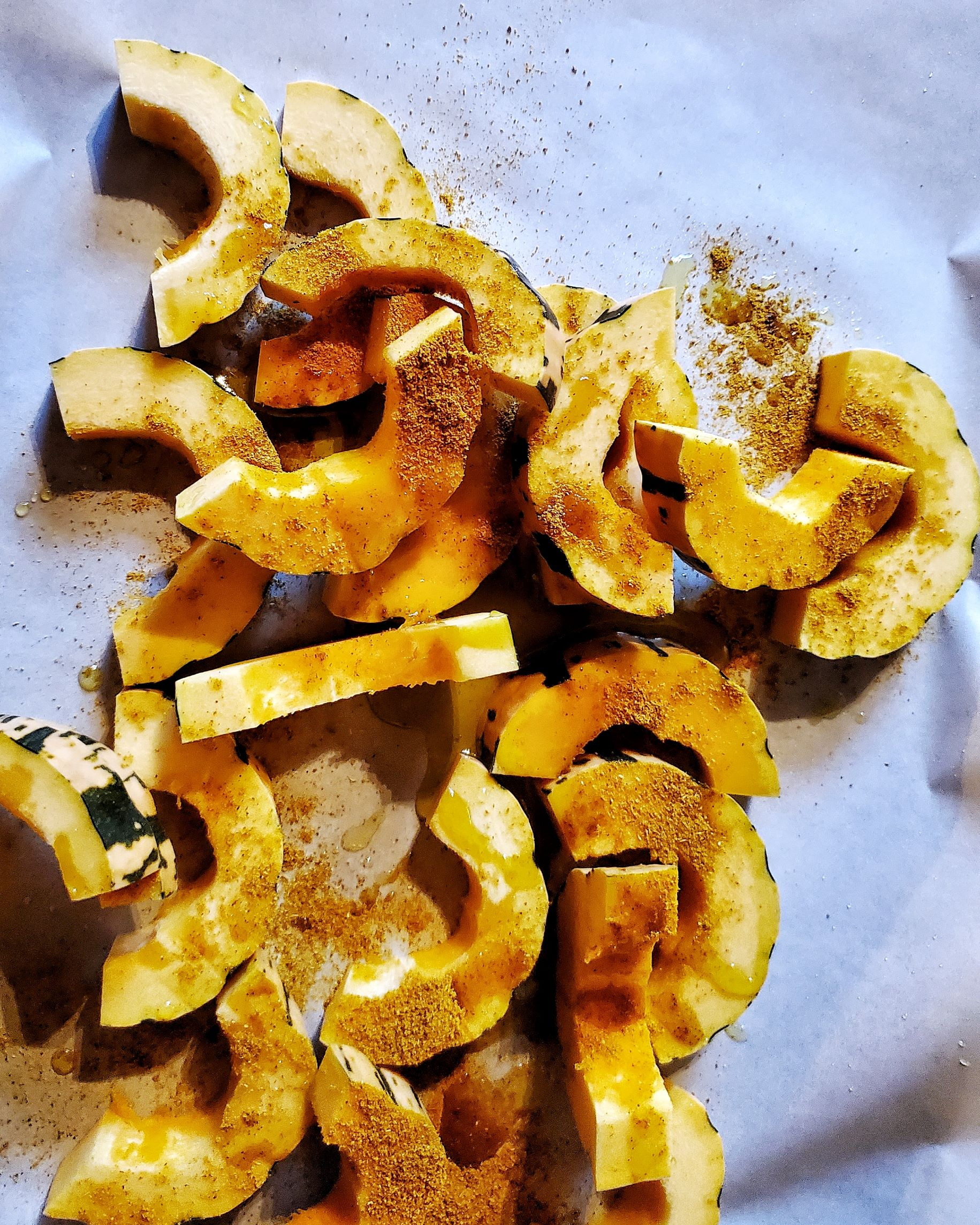 Squash slices with olive oil and curry powder on parhment