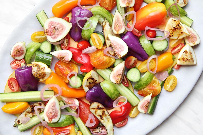 Sliced, colorful summer fruits and vegetables on a platter