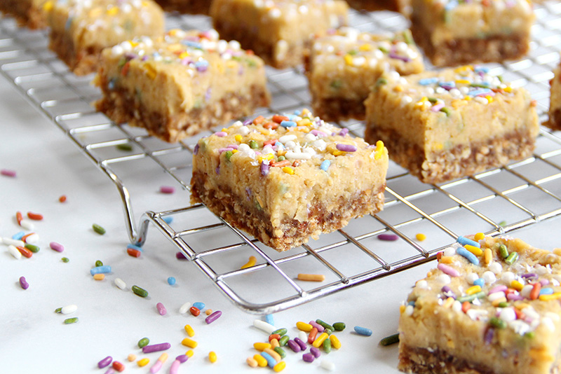 Birthday cake bars cut into squares on a cooling rack