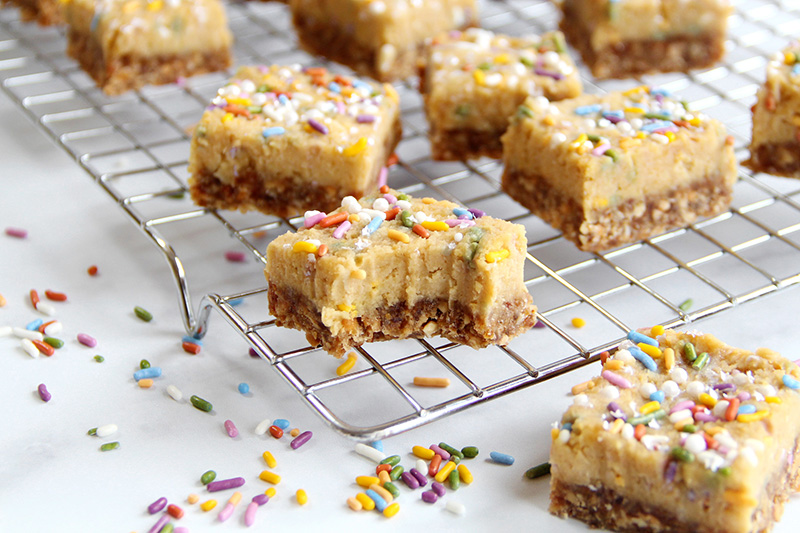 Birthday cake bars cut into squares on a cooling rack, with a bite mark