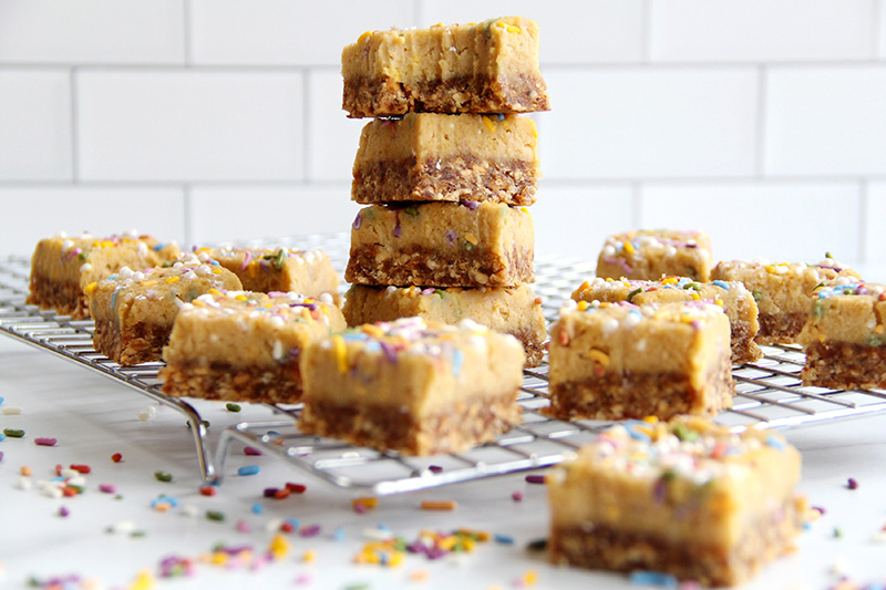 Stack of birthday cake bars on a cooling rack with a bite mark