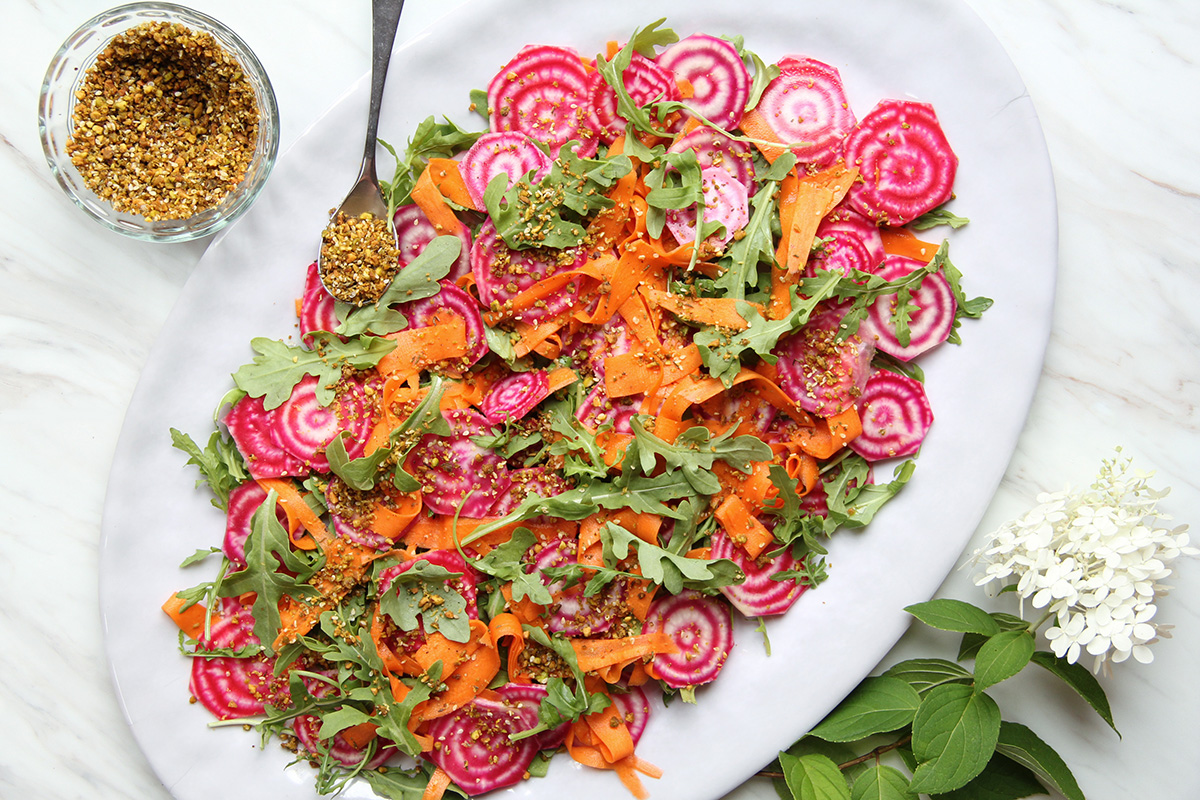 Colorful fall salad on a platter with dukkah and flowers