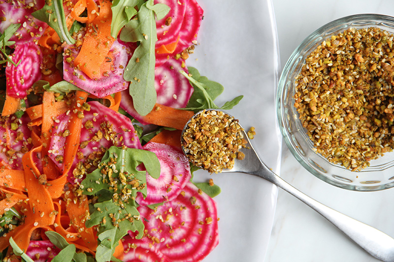 Colorful fall salad on a platter with spoonful of dukkah