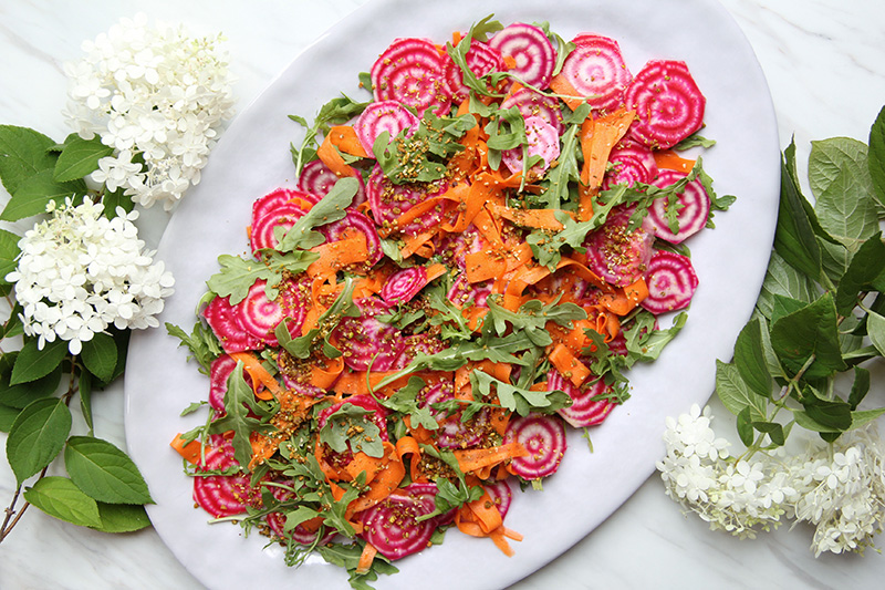 Colorful fall salad on a platter with flowers