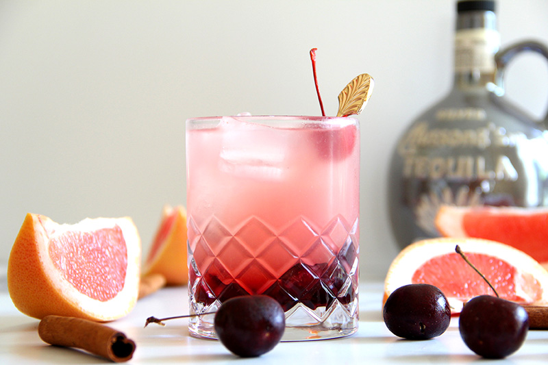 Cinnamon Cherry Paloma cocktail with a tequila bottle