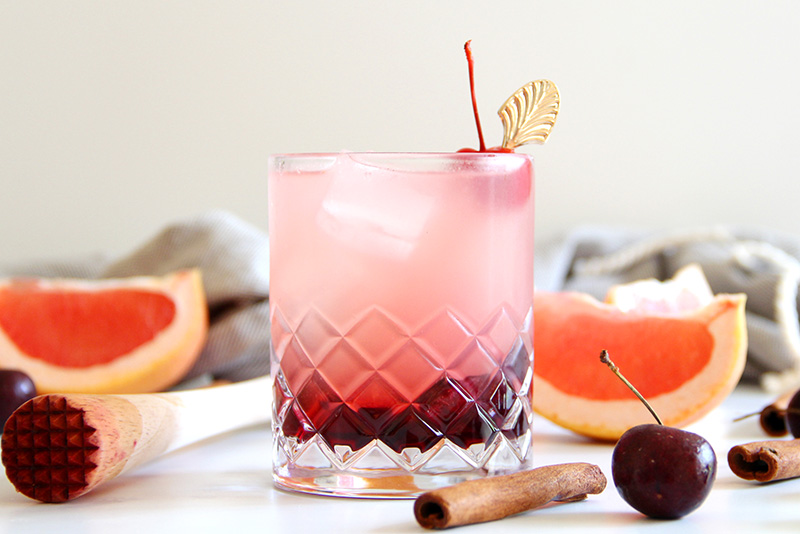Cinnamon Cherry Paloma cocktail with a muddler and ingredients