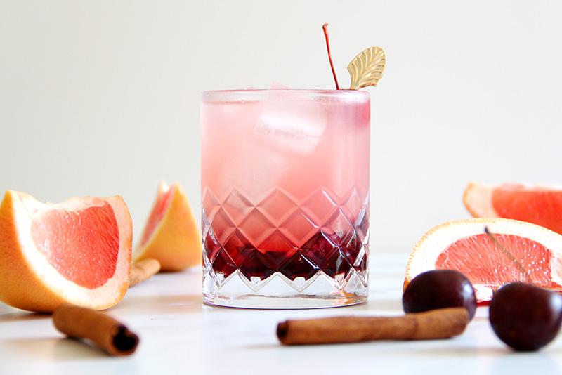 Cinnamon Cherry Paloma cocktail with grapefruit slices, cherries, and cinnamon sticks