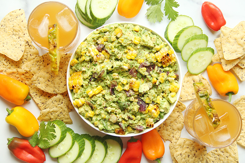 Grilled corn guacamole with veggies, chips, and cocktails