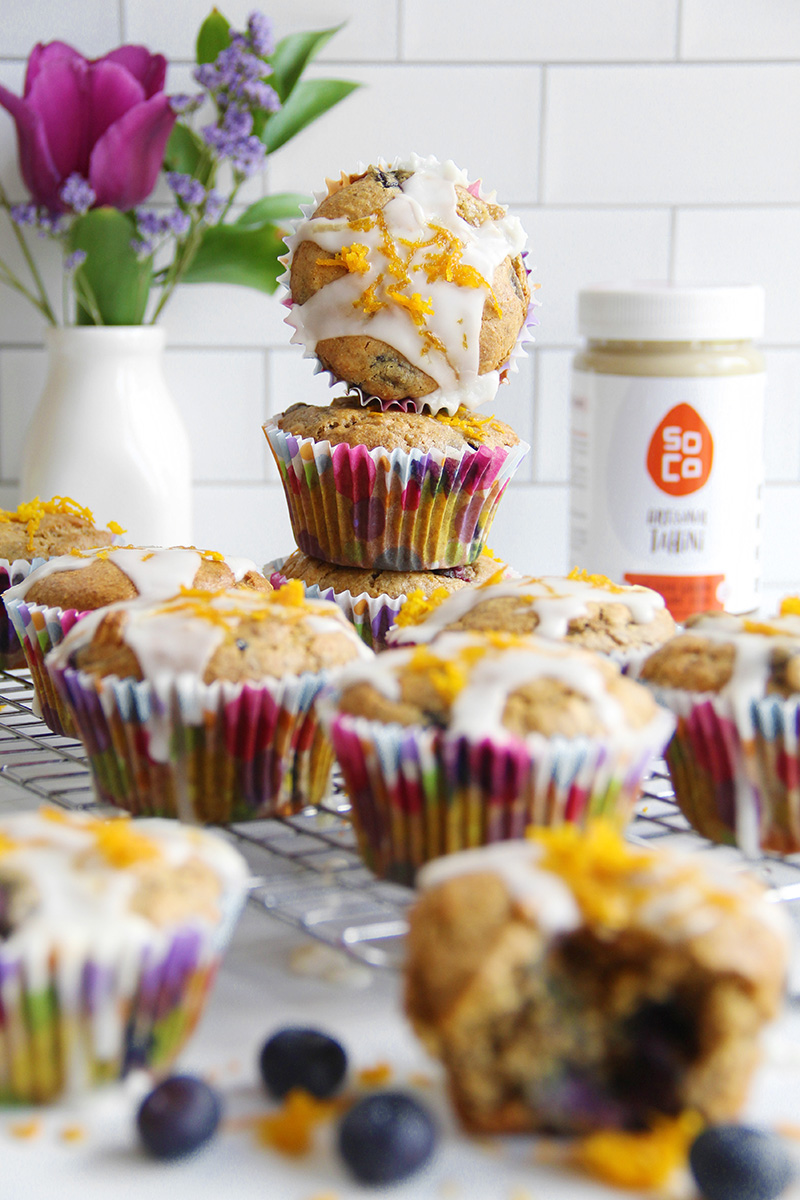 Orange ginger blueberry tahini muffins with icing, on a cooling rack, with a stack of muffins in the background
