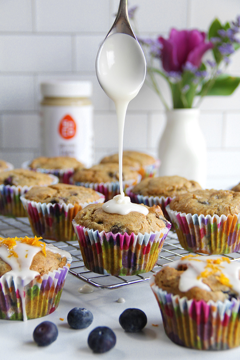 Drizzling icing onto orange ginger blueberry tahini muffins that are sitting on a cooling rack