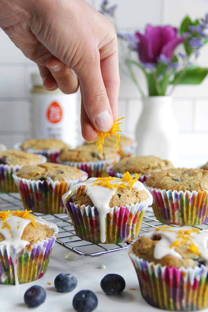 Adding orange zest on top of orange ginger blueberry tahini muffins that are sitting on a cooling rack