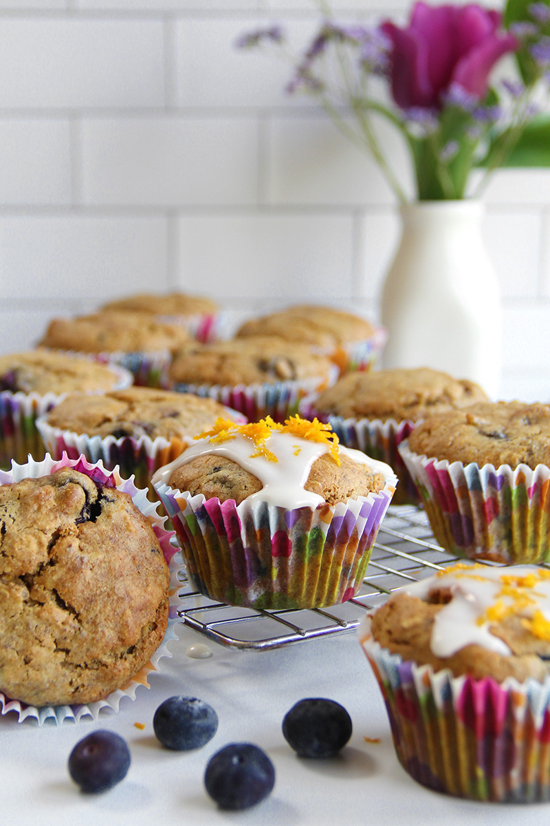 Orange ginger blueberry tahini muffins with icing, sitting on a cooling rack
