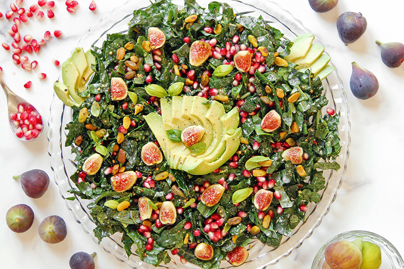 California Harvest Salad on a serving platter, with figs and pomegranate on the sides