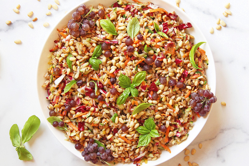 Colorful farro salad from above, with scattered pine nuts