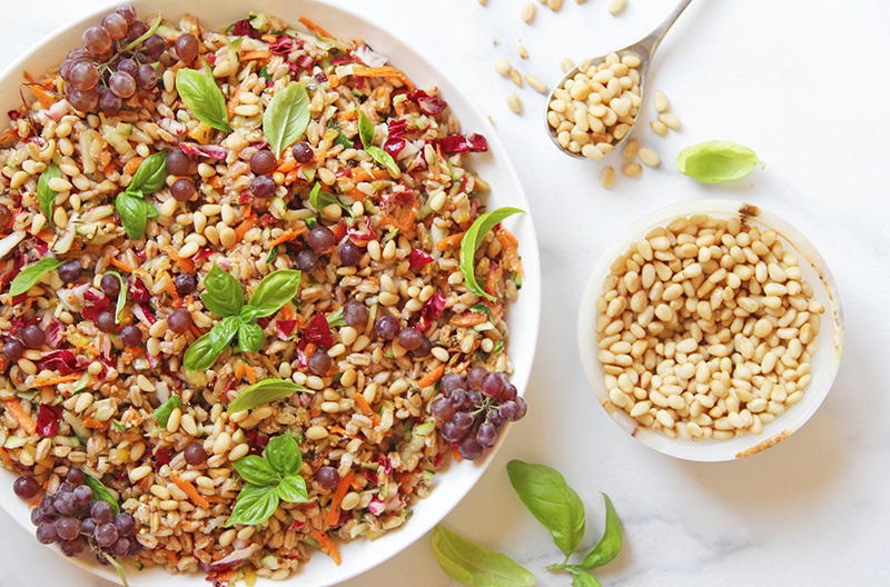 Colorful farro salad from above, with a dish of pine nuts