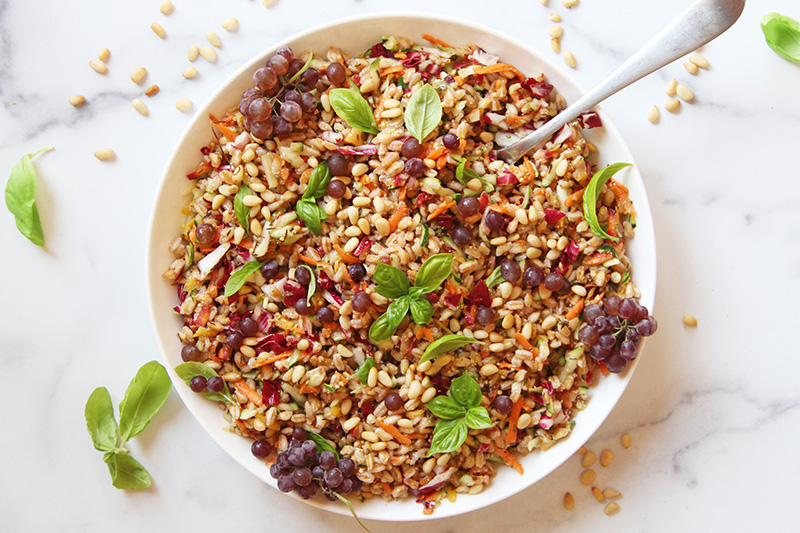 Colorful farro salad from above, with a serving spoon