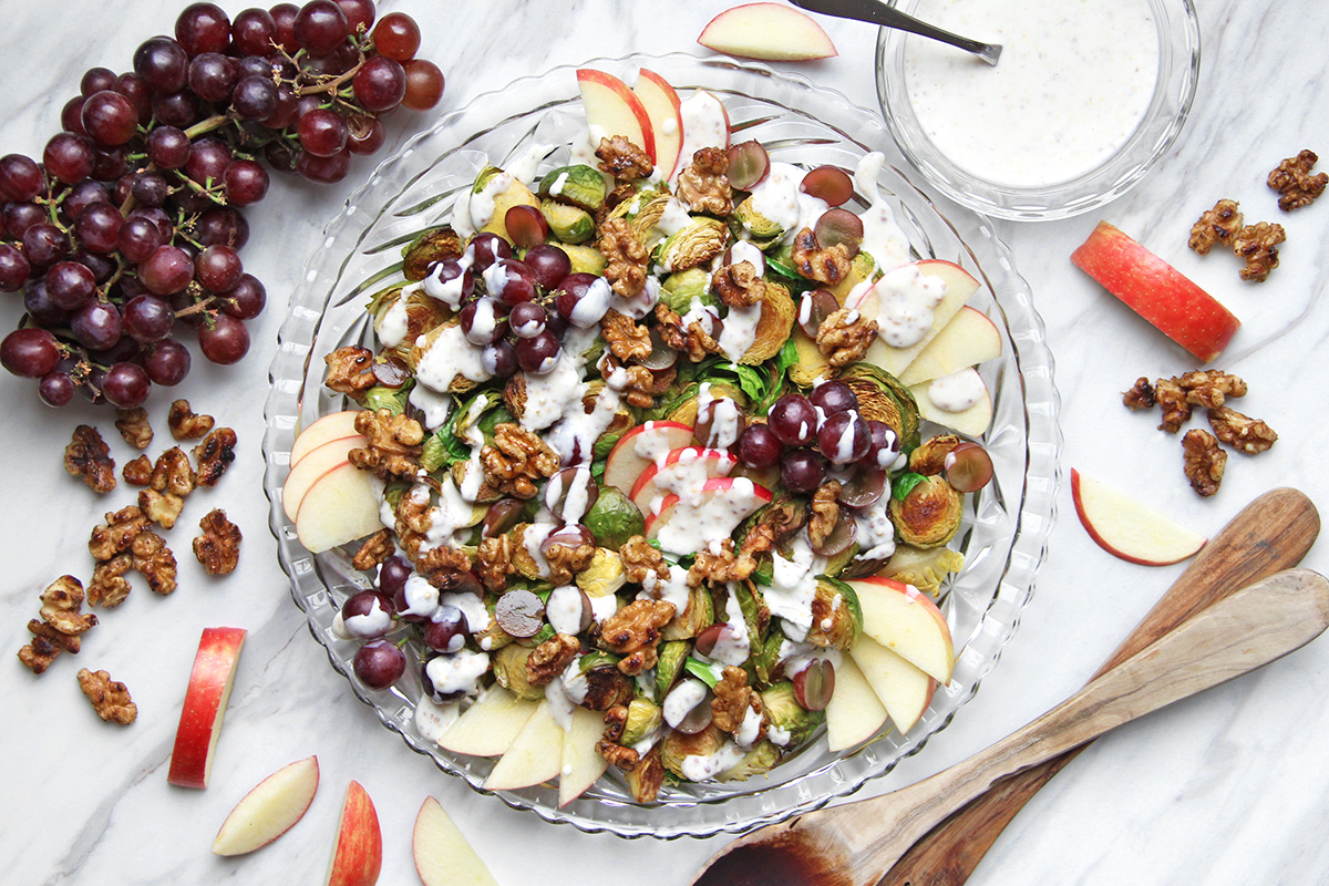 Roasted Brussel Sprout Waldorf Salad on a platter, with dressing and serving utensils