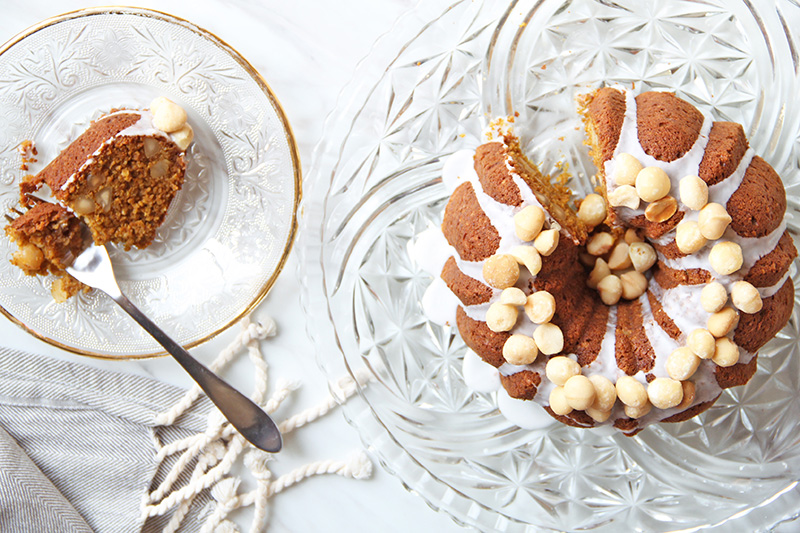 Pumpkin bundt cake topped with macadamia nuts, with one slice on a plate