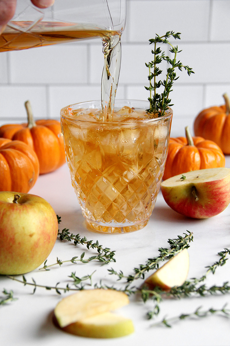 Apple Thyme Old Fashioned Cocktail being poured into a serving glass