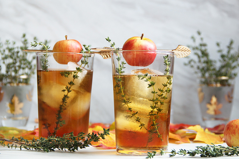 Apple Thyme Old Fashioned Cocktail garnished with whole baby apples and fresh thyme