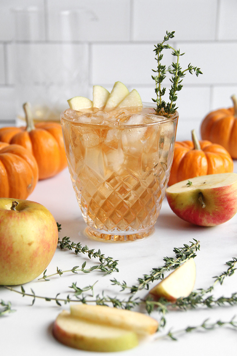 Apple Thyme Old Fashioned Cocktail garnished with apple slices and fresh thyme