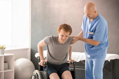 Young man getting into wheelchair