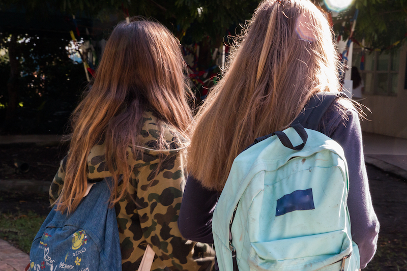 Two girls with backpacks on their way to high school