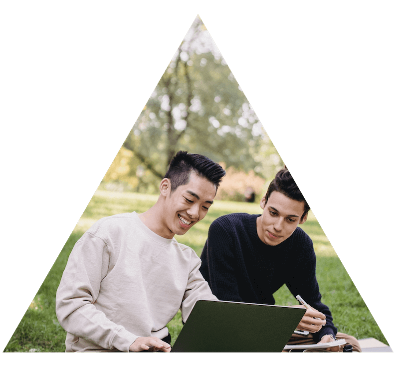 two guys sitting on lawn, using a laptop