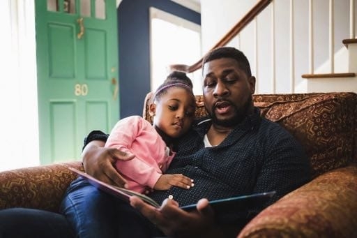 Father reading a book to his young daughter